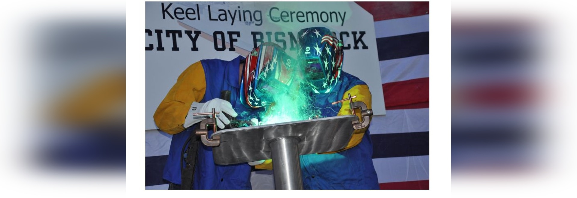 The Honorable Robert O. Wefald (right), former North Dakota State District Court Judge, welds his initials into the keel plate of the future USNS City of Bismarck (EPF 9) with the assistance of Aus...