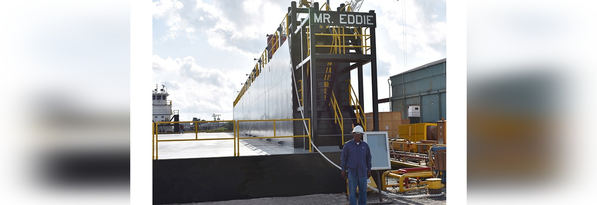 "Eddie Barnes, Jr., namesake for new dry-dock at Bollinger Quick Repair, Harvey, La. stands proudly in front of the ""Mr. Eddie"""