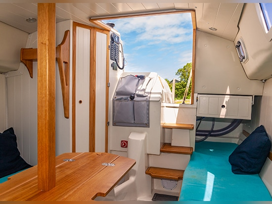 The wide, offset companionway allows easy access to the cabin around the engine box. The head compartment is to starboard.